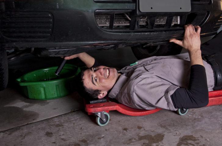 An auto mechanic working under a car doing an oil change