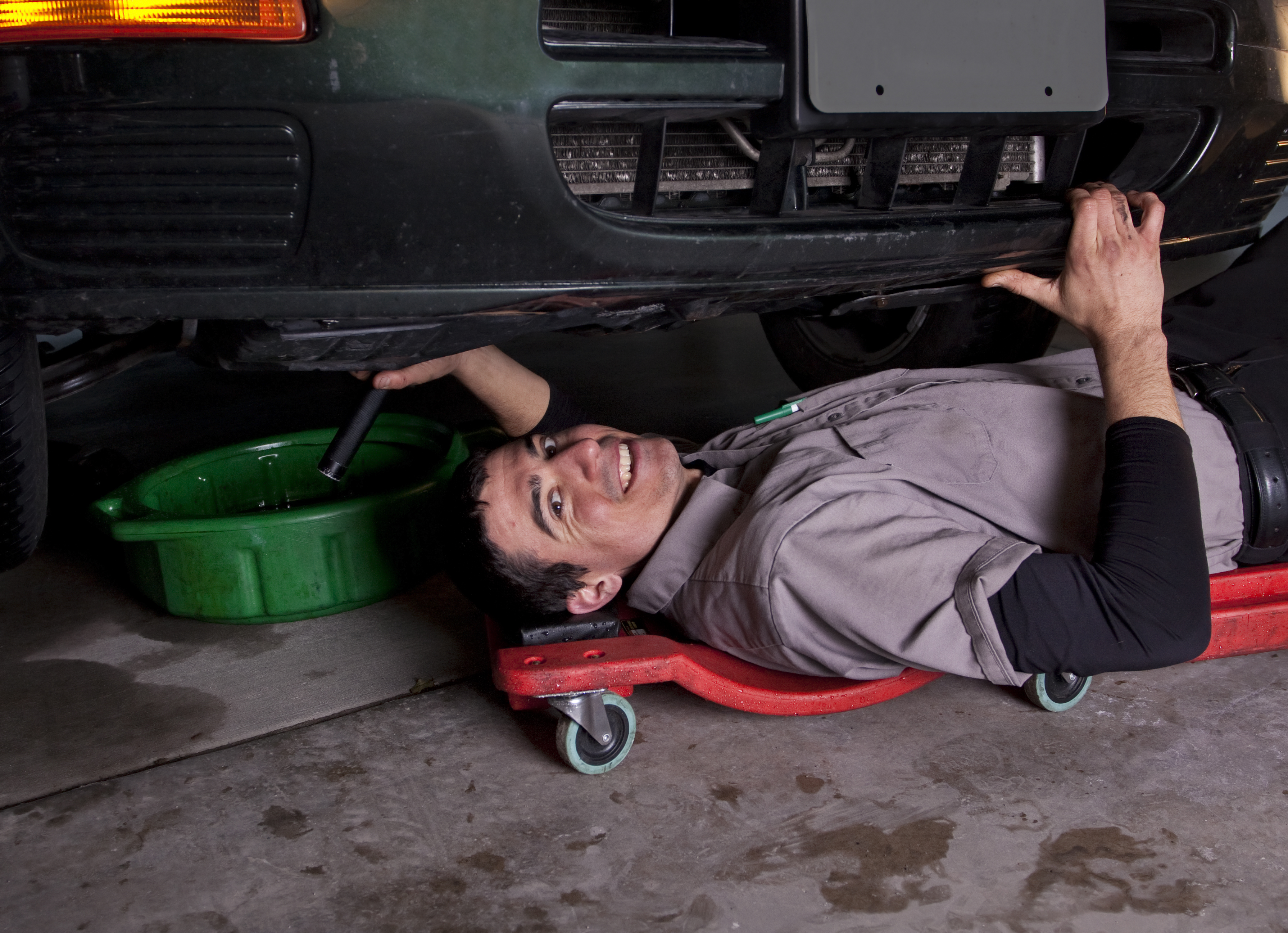 An auto mechanic working under a car doing an oil change